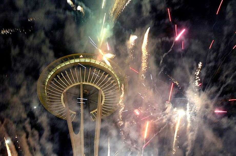 Fireworks explodes from the Space Needle, Jan. 1, 2008. The celebration was slightly delayed because of a computer glitch. Photo: P-I File