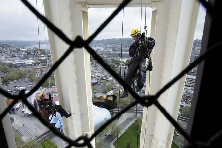 Matt Henry, left, and Matthew Waskiewicz, rope access technicians with Skala, lower themselves after using heated, high-pressure water to clean the surface of the Space Needle. The structure hadn't been cleaned with such tooks since its 1962 opening. Photo: P-I File