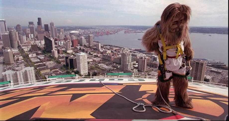Seattle Supersonics mascot Squatch prepares to unhook his harness after pretending to put the finishing touches on a new mural atop the Space Needle, June 1996. Photo: P-I File