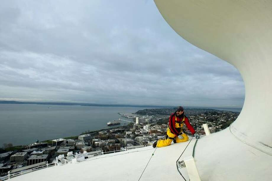 Brian Morningstar, working for Pyro Spectaculars about 530 feet above ground, adjusts his harness while helping to install roughly 2000 fireworks on the Space Needle, December 2008. Photo: P-I File