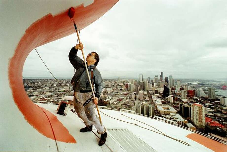 George Links of O'Mega Graphics battles winds of up to 30 mph to paint the top of the Space Needle, 2002. In honor of the landmark's 40th anniversary celebration, the pagoda roof of the landmark was painted the original Galaxy Gold, the primary color from the Century 21 paint scheme. Photo: P-I File