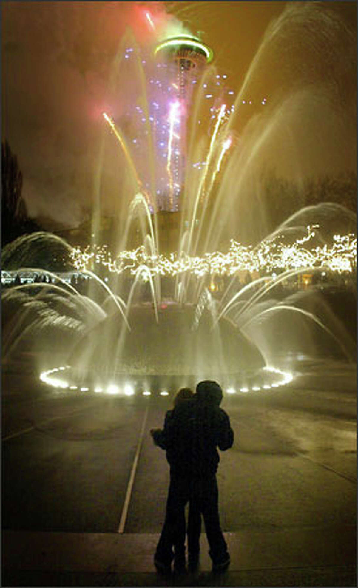 A couple embraces in front of the International Fountain at the Seattle Center as fireworks erupt from the Space Needle to signal the start of the New Year.