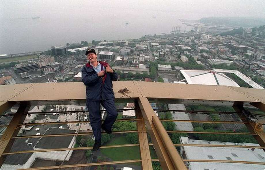 The 1997 photo caption read: Space Needle engineer Evan Pate seems to be enjoying his task as he works on the wiring for the fireworks show to celebrate the 35th anniversary of the Space Needle. Photo: P-I File