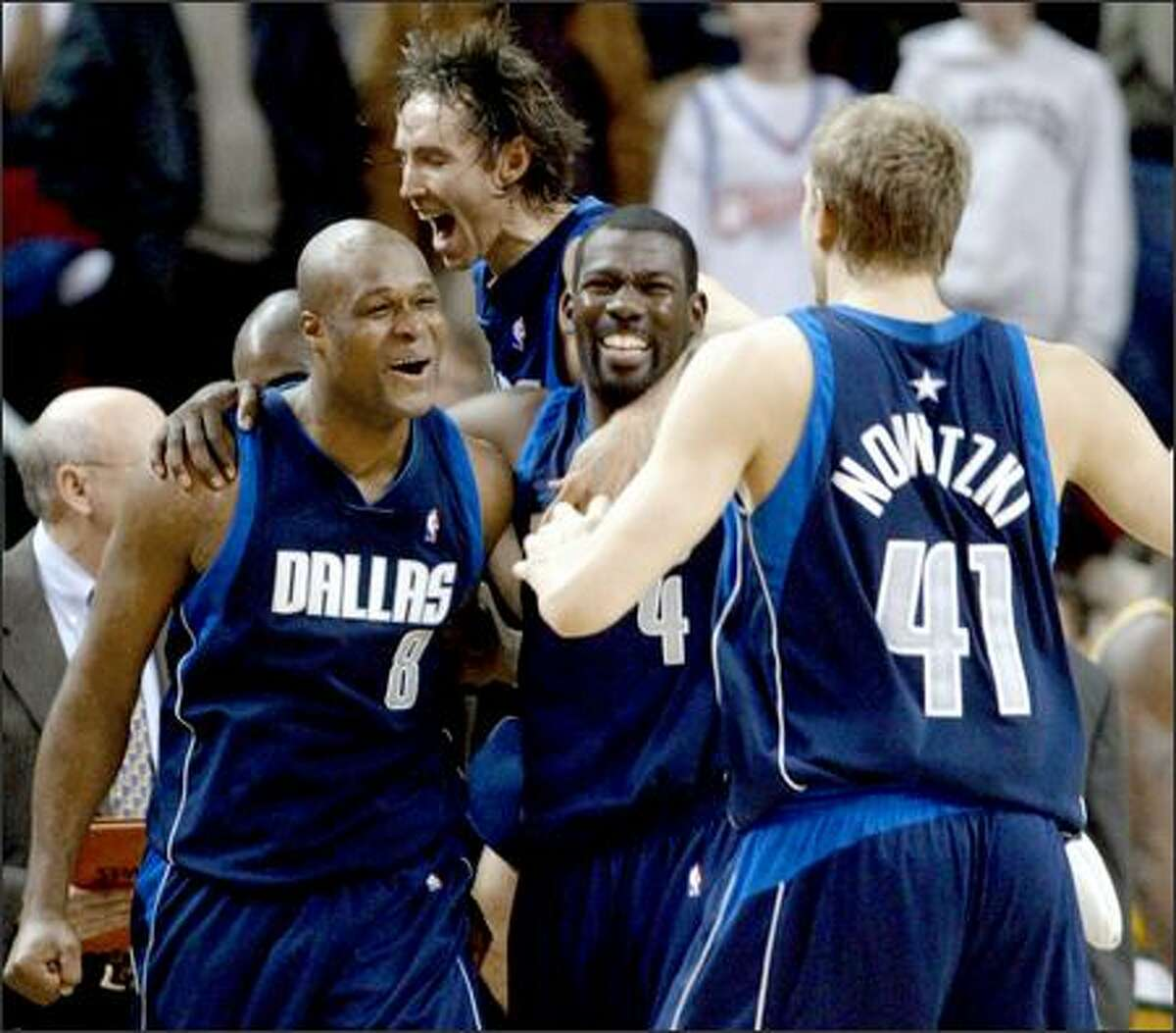 Dallas Mavericks players celebrate after Antoine Walker, left, made a last-second shot to win the game. Joining the party are Steve Nash, top, Michael Finley, center, and Dirk Nowitzki.