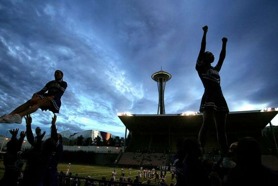 Garfield High School cheerleaders go through their routines as they battle Franklin at Memorial Stadium in the shadow of the Space Needle, Oct. 17, 2003. Photo: P-I File