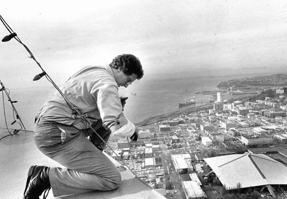 The 1987 photo caption read: Kevin Smith, lead engineer for the Space Needle, attaches a string of lights to the city's tallest Christmas light display, at the top of the Space Needle. Photo: P-I File
