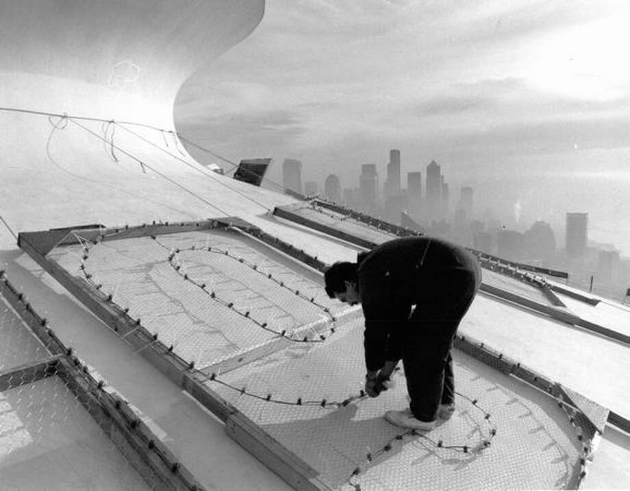 The December 1991 photo caption read: Perched atop the Space Needle, Ken Willanger puts together lights on giant numerals that will herald the arrival of 1992 on New Year's Eve. Photo: P-I File