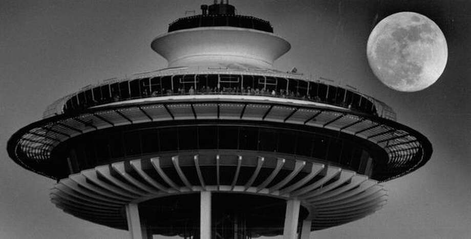 The February 1992 photo caption read: Visitors to the Space Needle yesterday gathered on the observation deck to watch the sun set over the Olympic Mountains. In the process, they missed another cosmic event - the moon rising behind them. (Grant M. Haller/Seattlepi.com file) Photo: P-I File