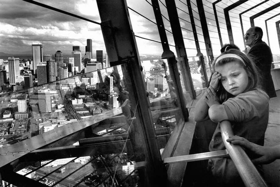 The July 1990 photo caption read: It's a dizzying view from the Space Needle's observation deck to the city below and the mountain ranges beyond. Photo: P-I File
