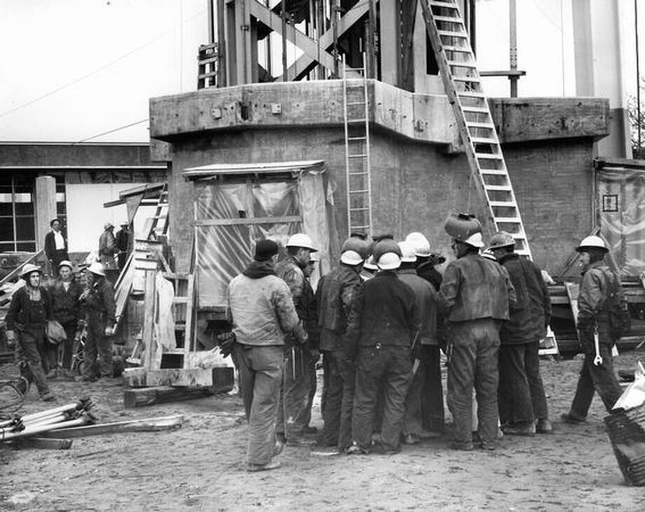 The December 1961 photo caption read: Ironworkers huddle at base of Space Needle during a 15-minute work stoppage caused by jurisdictional dispute with carpenters. Photo: P-I File