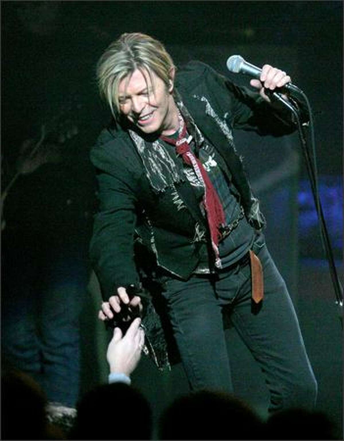David Bowie borrows sunglasses from a fan because of the bright spotlights at the Paramount during his performance.