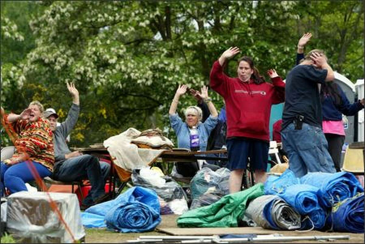 Residents of Tent City 3 at the Lake City Christian Church wave goodbye to their neighbors who were moving to Tent City 4 in Bothell on May 17. Thirty went to Bothell and another 65 or so moved to a site in Seattle's Central District. Said Dawn Lopez (left), who had been evicted from a Greenwood home: