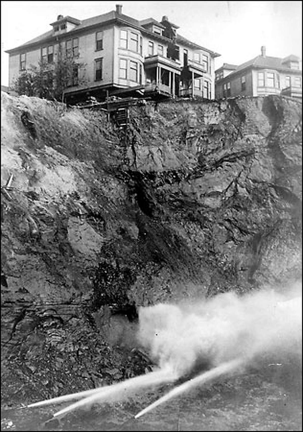 Denny Regrade, 1908: Denny Hill was a steep and inconvenient bump on the north side of downtown Seattle until it was flattened nearly a century ago by city engineers. The regrading of Denny Hill first began in 1898 and carried on in various phases until 1930. It was only one of several projects to level the city, or at least make its hills more easily navigable. Some property owners, including those who owned the homes in this photo at the foot of Blanchard Street, delayed selling out as the city sluiced around them. At times houses were left on their own individual pedestals, with ladders as the only means of access.