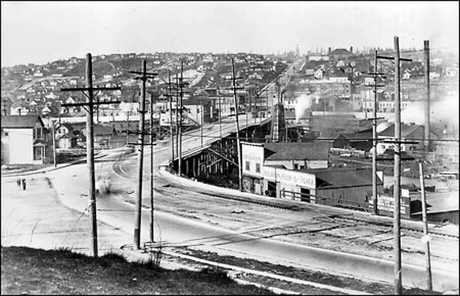 Road to Fremont, 1915: A wooden trestle once crossed the slough that was to become the Lake Washington Ship Canal. Shown here in a view from Fulton Street and Dexter Avenue North, the trestle was replaced with the new Fremont Bridge in 1917. The old Stone Way Bridge five blocks to the east was then eliminated. Photo: Seattle Post-Intelligencer