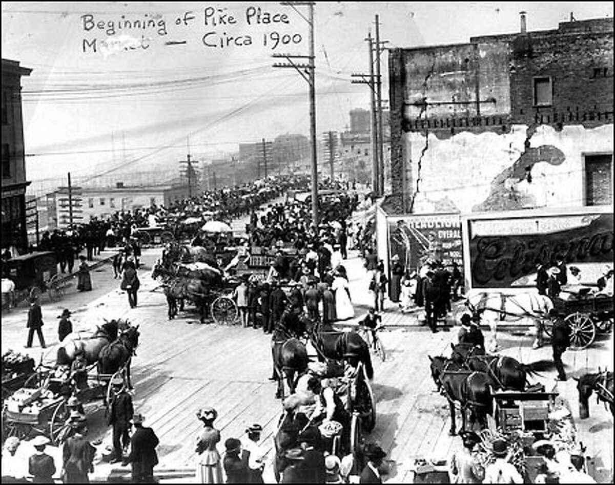 On the way to market, circa 1900: Before the Pike Place Market opened, farmers and shoppers traded along Western Avenue, seen in the distance. Demand for space soared as small farms, often tended by immigrants, spread through Rainier Valley and river valleys south and east of Seattle. The Market Arcade opened in 1907, followed by the Sanitary Market in 1910.