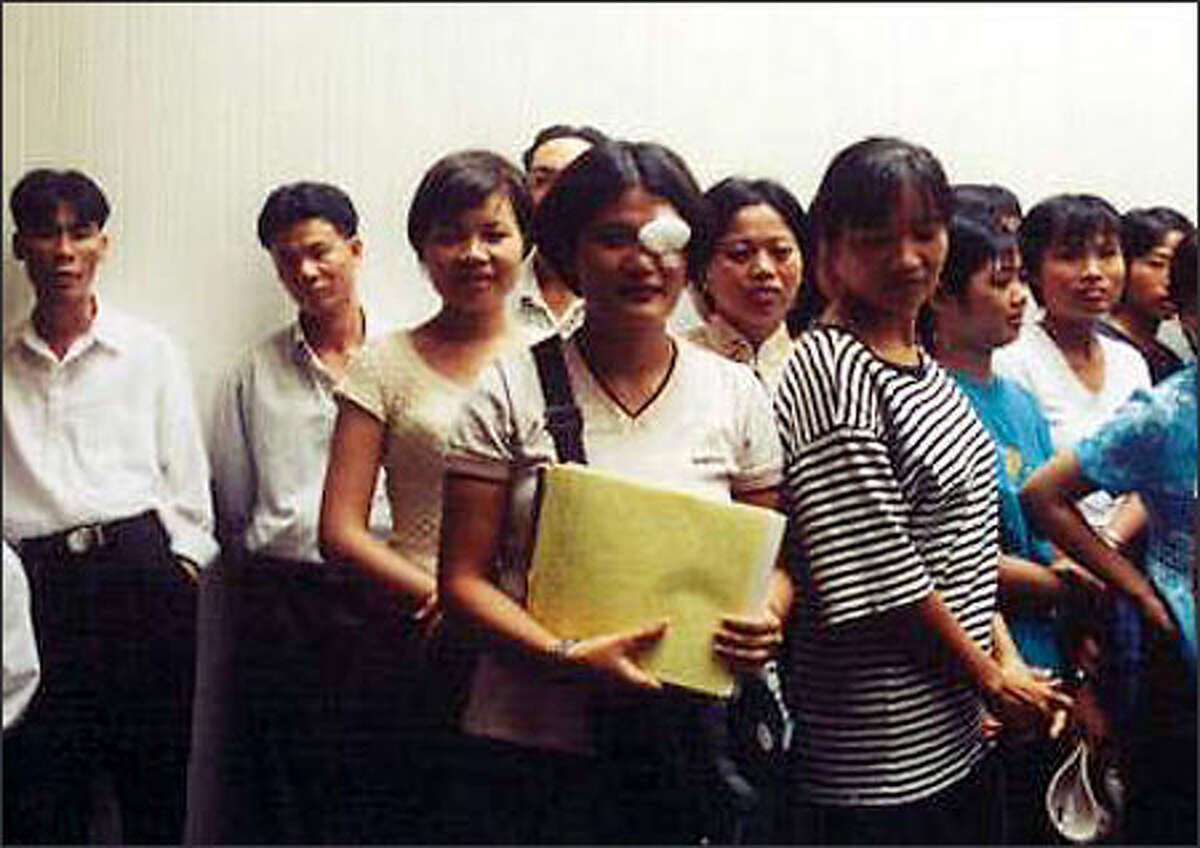 Workers from the factory gather outside a courtroom in in Pago Pago, American Samoa, on Jan. 16, 2001, for the start of a civil trial to recover back wages.