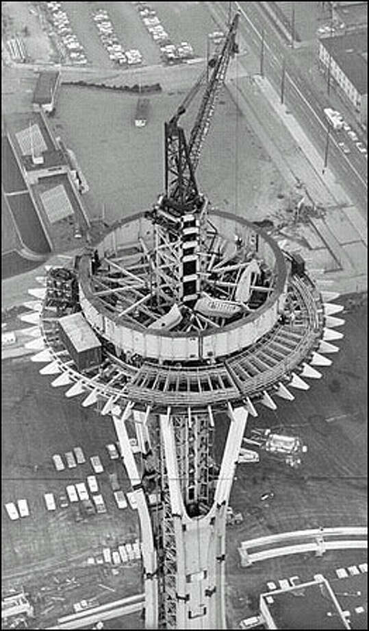 "Original caption: ""This unusual view of the World's Fair Space Needle was shot by Post-Intelligencer photographer John Vallentyne from a Seattle Police helicopter piloted by Patrolman Gordon D. Grosvenor. Thick ring in center is ring girder to hold out-rigger brackets that will support observation platform. Lattice-like sections in foreground are sections of restaurant turntable which will make one revolution an hour. On ground (bottom of picture, right) are monorail beams on which trains will ride."" Photo taken in 1961. Photo: Seattle Post-Intelligencer"