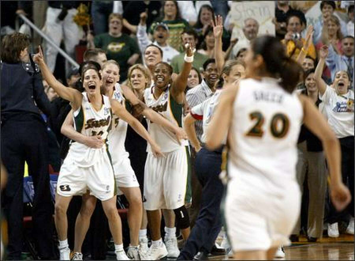 Seattle Storm players celebrate their first WNBA title after beating the Connecticut Sun 74-60 in the deciding Game 3 at KeyArena.