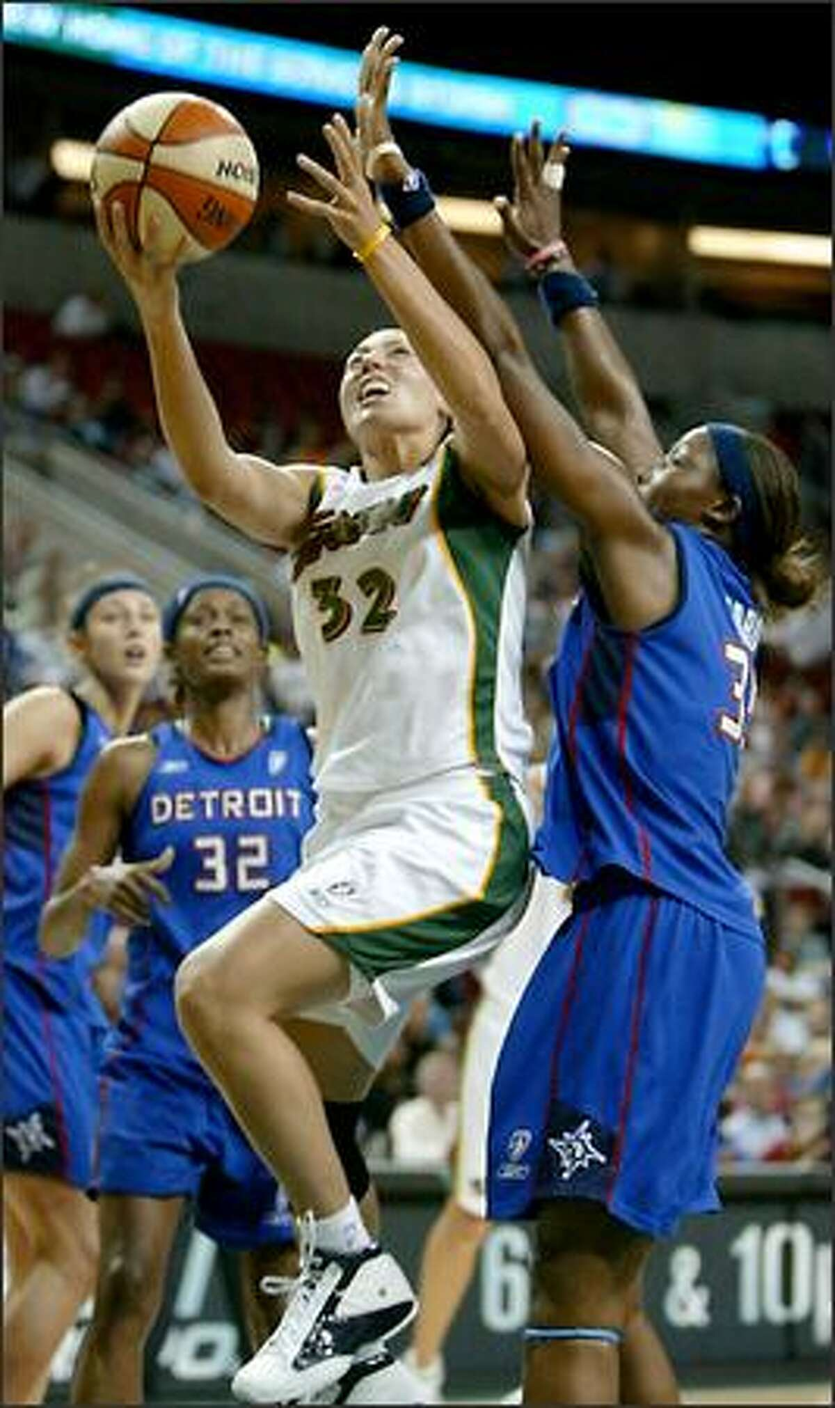 Seattle's Adia Barnes drives to the hoop as Detroit's Cheryl Ford tries for the block.