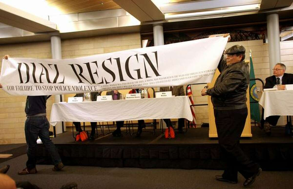 Federico Martinez, left, and Juan Jose Bocanegra interrupt a meeting with a banner calling for Seattle Police Chief John Diaz, far right, to resign during a panel discussion on police accountability on Thursday, February 3, 2011 at Seattle City Hall. Recent controversial police incidents prompted the at times rowdy forum.