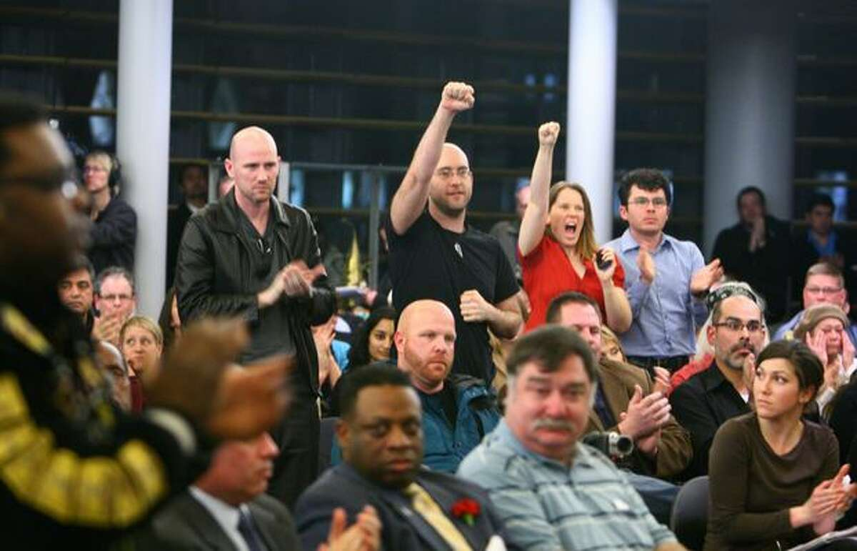 Audience members cheer after a statement was made during a panel discussion on police accountability on Thursday, February 3, 2011 at Seattle City Hall. The panel was organized after recent controversial incidents, including the August shooting death of Native wood carver John T. Williams by a Seattle Police officer.