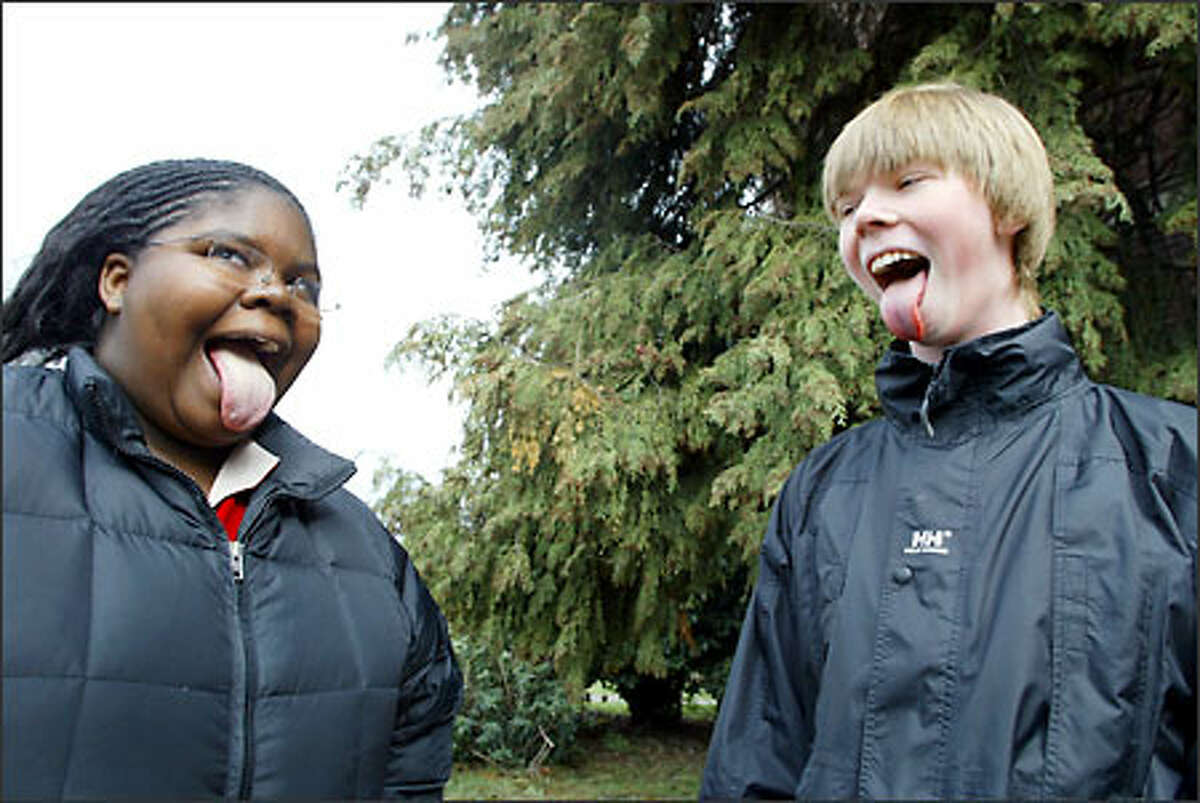 At lunch hour, friends Jossie Hicks, 15, left, and Aric Skurdal, 15, whimsically check to see whose tongue is longer. Both play violin in the orchestra. Hicks commutes to Garfield from the University District, while Skurdal travels to the school from Meadowbrook.