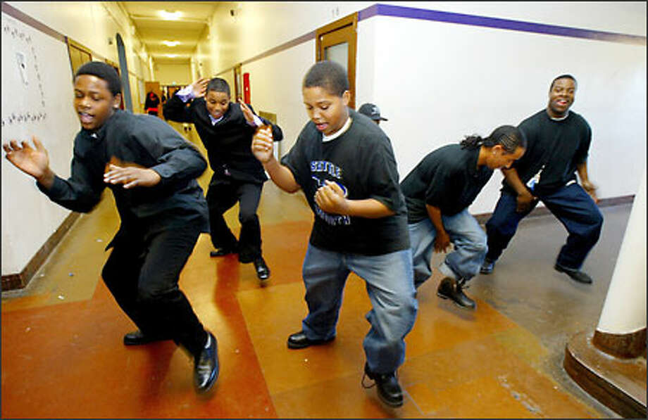 John Lyons, left, Jason Wilson, center, and Clayton Kadushin, second from right, work the Garfield hallways with a dance routine for the Seattle Smooth Sigma Beta Club in 2004. Photo: Meryl Schenker, Seattle Post-Intelligencer