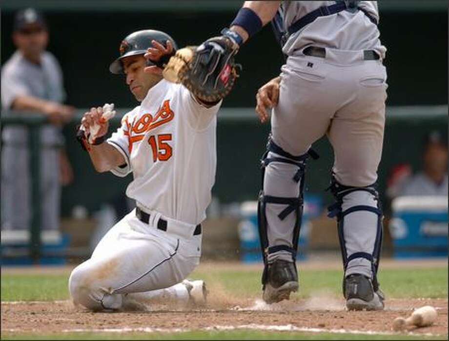 Baltimore's Jerry Hairston Jr. scores the go-ahead run ahead of the tag by Mariners catcher Miguel Olivo in the seventh inning. Hairston scored on a double by Larry Bigbie. The Orioles won 9-7 in the first game of a double header (AP Photo/Gail Burton) Photo: Seattle Post-Intelligencer