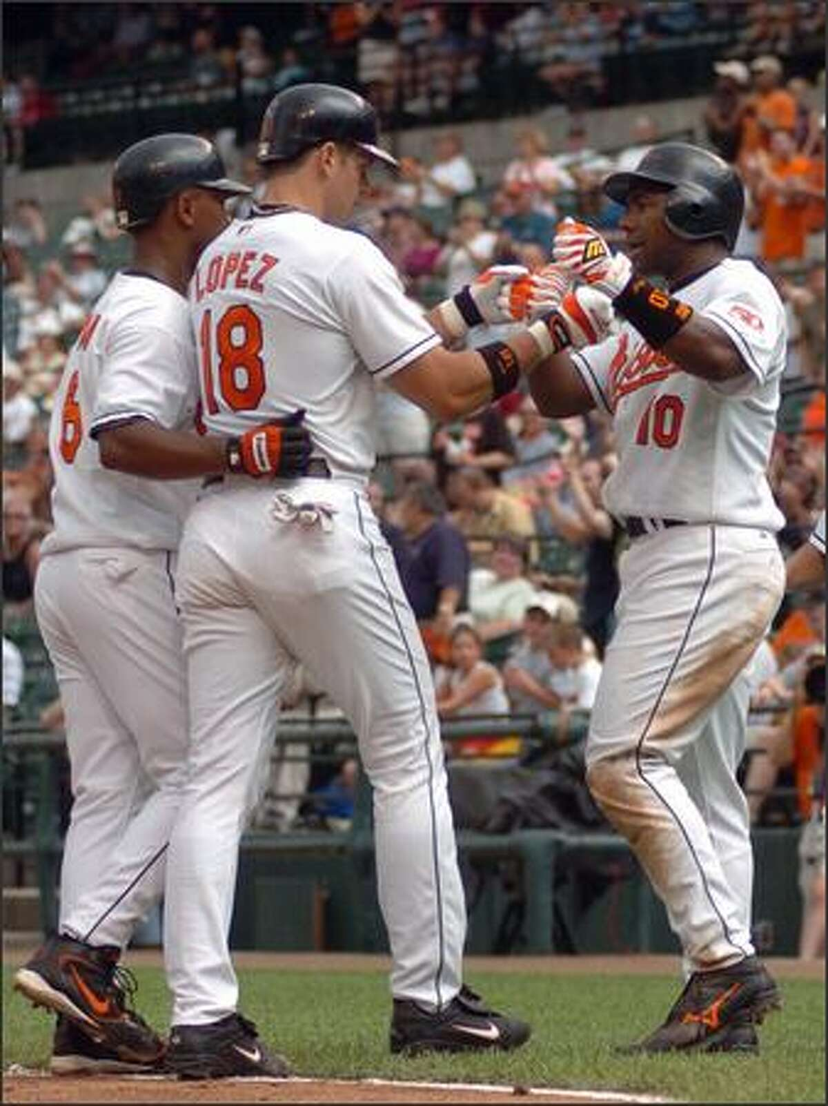 Baltimore Orioles' Javy Lopez (18) is congratulated by teammates Melvin Mora and Miguel Tejada (10) after hitting a three-run homer off Seattle's Ron Villone in the third inning of Game 1 of their double header. The Orioles won, 9-7. (AP Photo/Gail Burton)