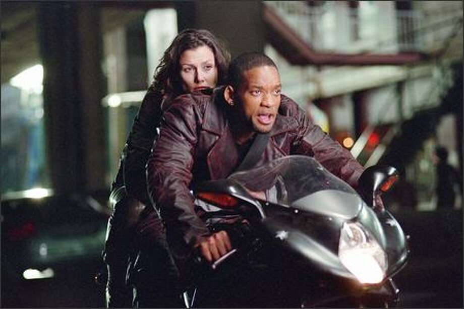 Detective Del Spooner (Will Smith) and Dr. Susan Calvin (Bridget Moynahan) race to stop a threat to the citizens of Chicago -- and possibly, to the entire world. The story takes place 30 years from now on a technological and social precipice, as the number of robots in the U.S. is about to triple. Photo: Ava Gerlitz