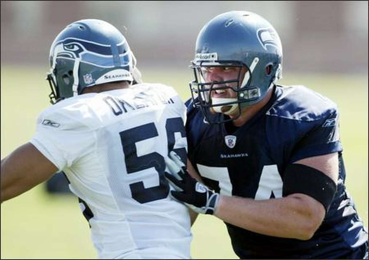 Offensive lineman Matt Hill (right) blocks defensive end Chike Okeafor during a pass rushing drill.