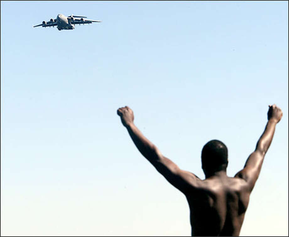 Fred Dumas of Seattle, who said he's been coming to the hydro races for 20 years, watches enthusiastically as a U.S. Air Force C-17 make a pass over Lake Washington. Photo: Dan DeLong, Seattle Post-Intelligencer