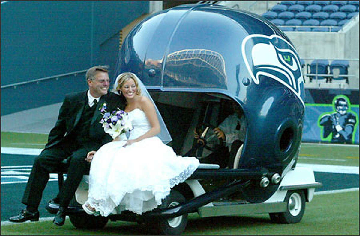 Bride Alexis Russo and her father, Guy Russo, ride into the stadium on the Seahawks victory helmet.