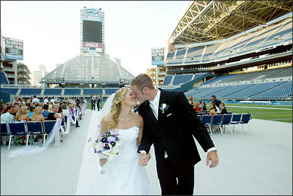 Chris and Alexis kiss as they walk up the aisle after the ceremony. The newlyweds are so into the Seahawks that they planned to postpone their honeymoon for a day so they could watch Monday night's preseason game against the Green Bay Packers.