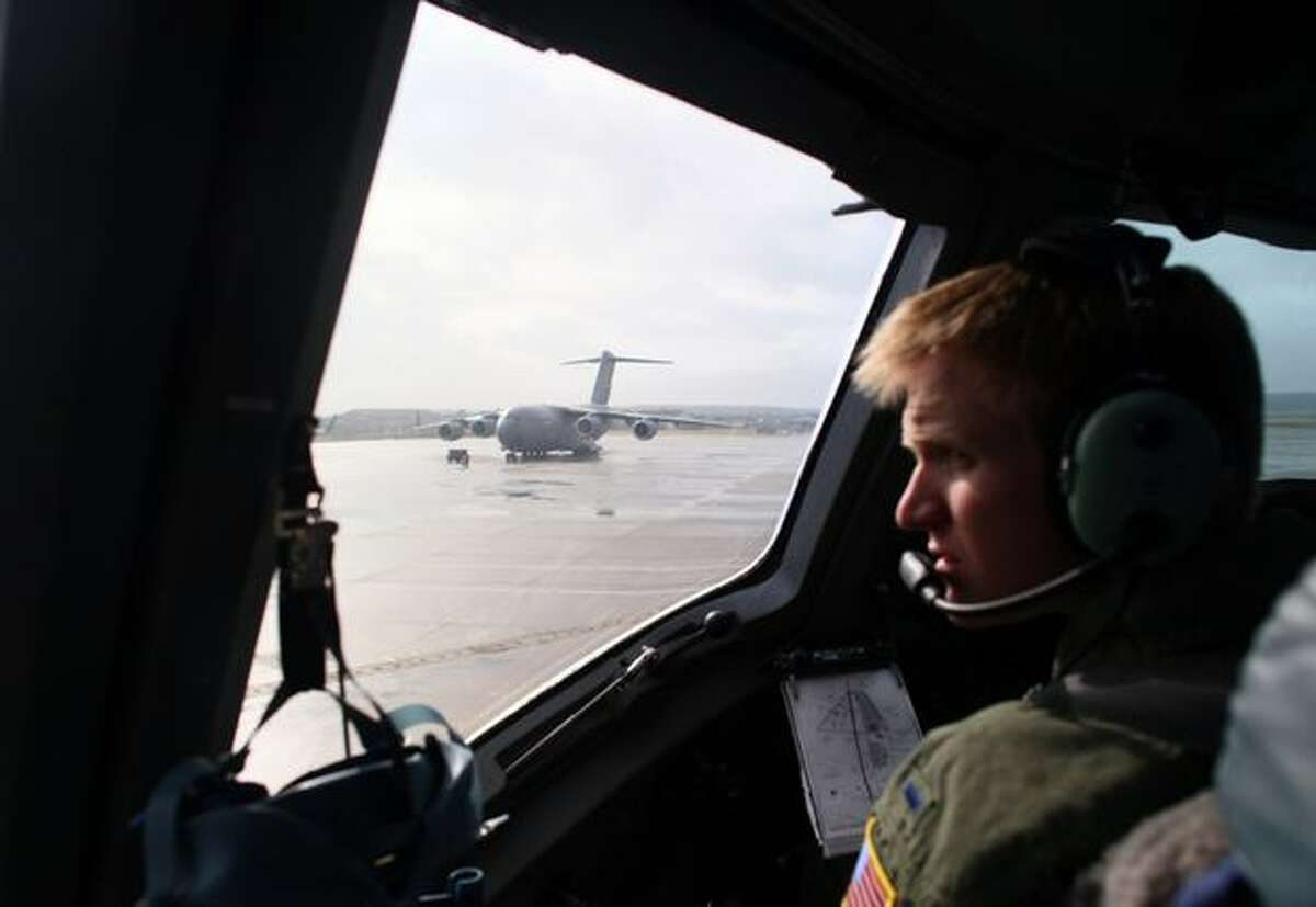 U.S. Air Force Lt. Joe Hurley sits in the copilot seat as he and Capt. Tony Cappel begin to taxi a C-17 Globemaster III at Langley Air Force Base for the trip into Haiti days after an earthquake ravaged the island nation. The aircraft carried supplies for the rescue and recovery operation and evacuated almost 200 people out of the country. The situation at the Port-au-Prince airport was unpredictable and chaotic when the aircraft arrived on on Sunday, January 17, 2010. The massive 7.0 earthquake that leveled much of Port-au-Prince is reported to have killed nearly 200,000 people, and injured or maimed countless others.