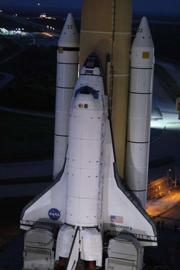 Space shuttle Discovery rolls out of NASA's vehicle assembly building atop a crawler transporter to launch pad 39 A at Kennedy Space Center in Cape Canaveral, Fla. Photo: Getty Images