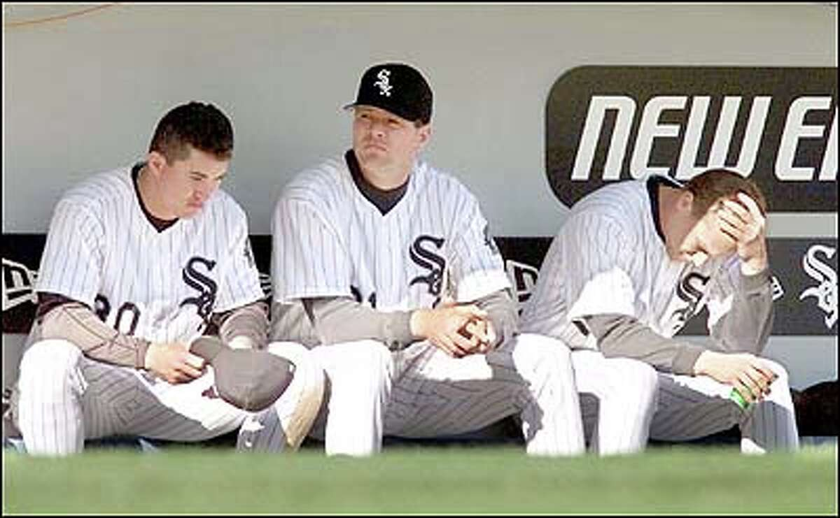 Magglio Ordonez, Cal Eldred and Jeff Abbott react in the dugout in the 9th inning as the Mariners win 5-2.