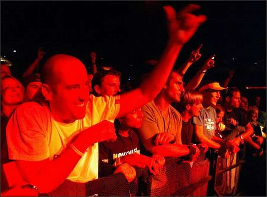 Fans bathed in red light from the stage react to Pearl Jam's performance at the Showbox on Friday night.