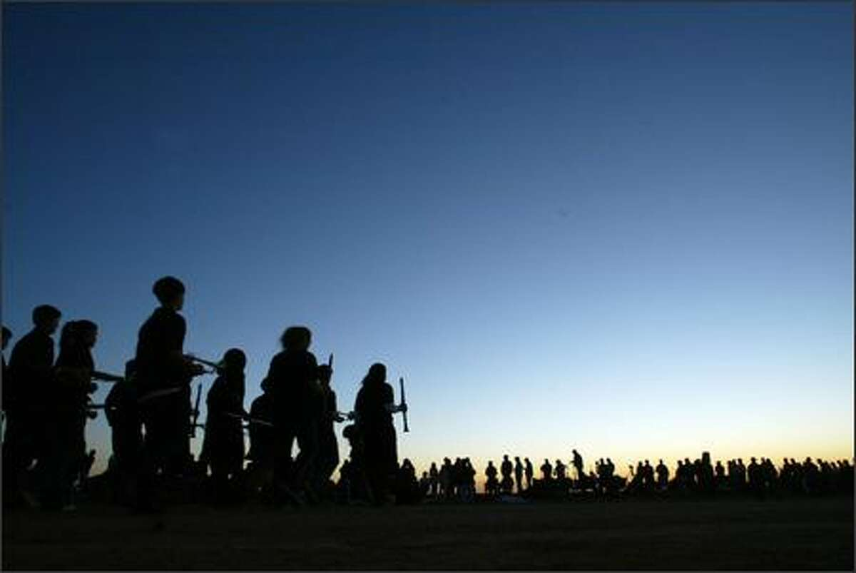 The Foothills High School marching band marches to the view line in the early morning pre-sunrise light.
