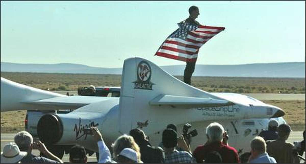 Brian Binnie holds the American Flag as he takes a victory lap on SpaceShipOne after the flight.