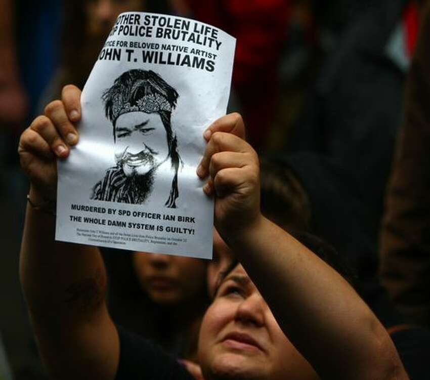 A woman holds up a picture during a protest after the recent police shooting of Native American carver John T. Williams in Seattle. Williams was shot and killed by a Seattle Police officer while holding a knife he did not put down when ordered. Williams used the knife to carve small totems and was deaf in one ear.