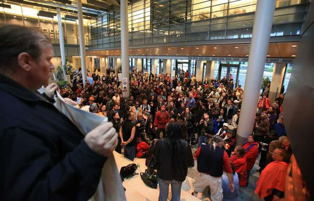 People gather in City Hall during a protest over the recent police shooting of the Native American carver John T. Williams in downtown Seattle. Williams was shot and killed by a Seattle Police officer while holding a knife he did not put down when ordered. Williams used the knife to carve small totems and was deaf in one ear.