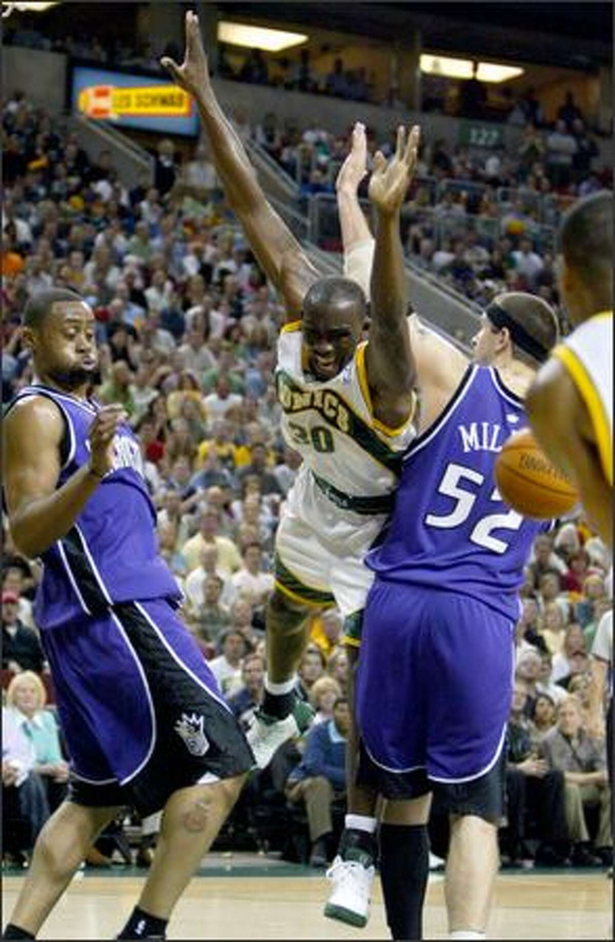 The Sonics' Reggie Evans goes airborne as he is fouled by Sacramento's Brad Miller, right.