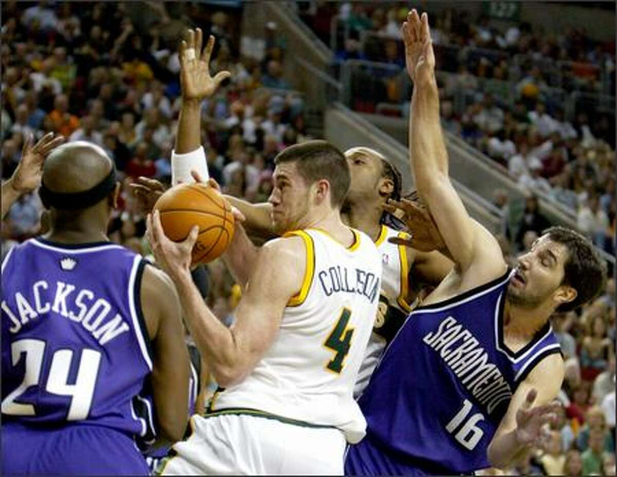 Sonics forward Nick Collison grabs a rebound between Bobby Jackson and Peja Stojakovic of the Kings. Collison's teammate Danny Forston is in the rear.