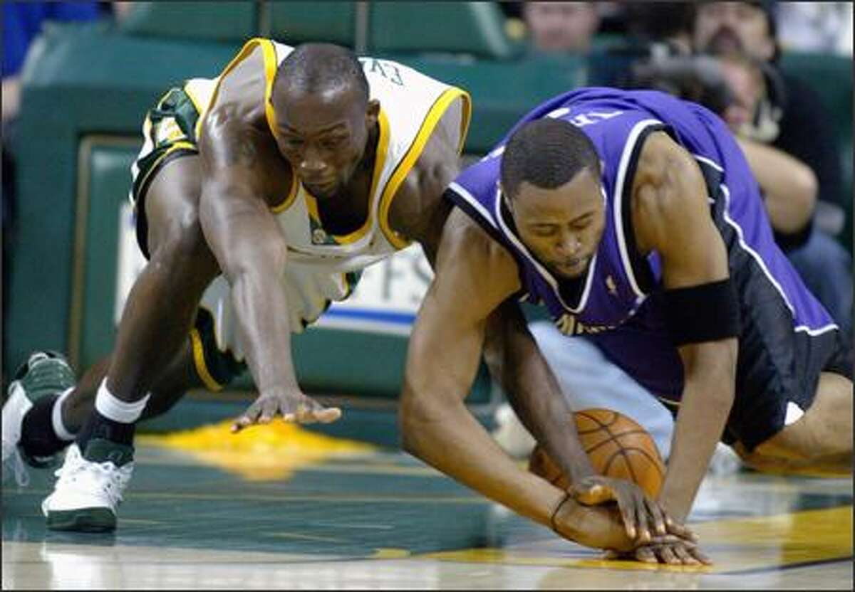 The Sonics' Reggie Evans battles the Kings' Kenny Thomas for a loose ball. Evans scored seven points in the first 7:06 of the game and was tied with teammate Ray Allen for most points in the first quarter.