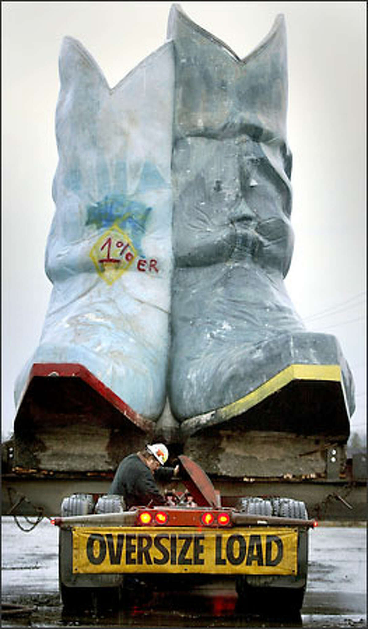 Mike Hougardy, working for general contractor Sundstrom, secures a 110,000-pound pair of boots onto a flatbed on West Marginal Way. The structure, along with an equally large cowboy hat, was moved to nearby Oxbow Park.Trujillo:
