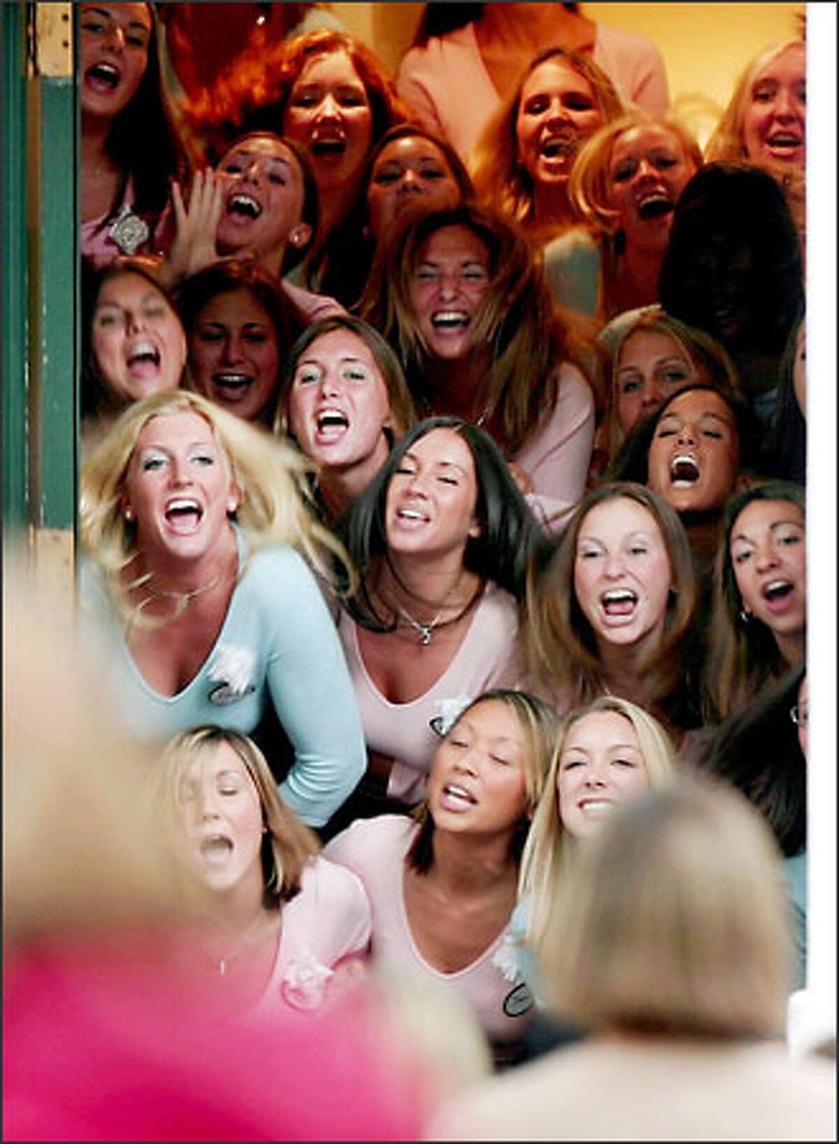 Members of Pi Beta Phi poke their heads out of the front door of their sorority house as they sing and chant to rushees along Greek row at the University of Washington. This is rush week, when students tour sororities and fraternities to see whether Greek life appeals to them.Trujillo: