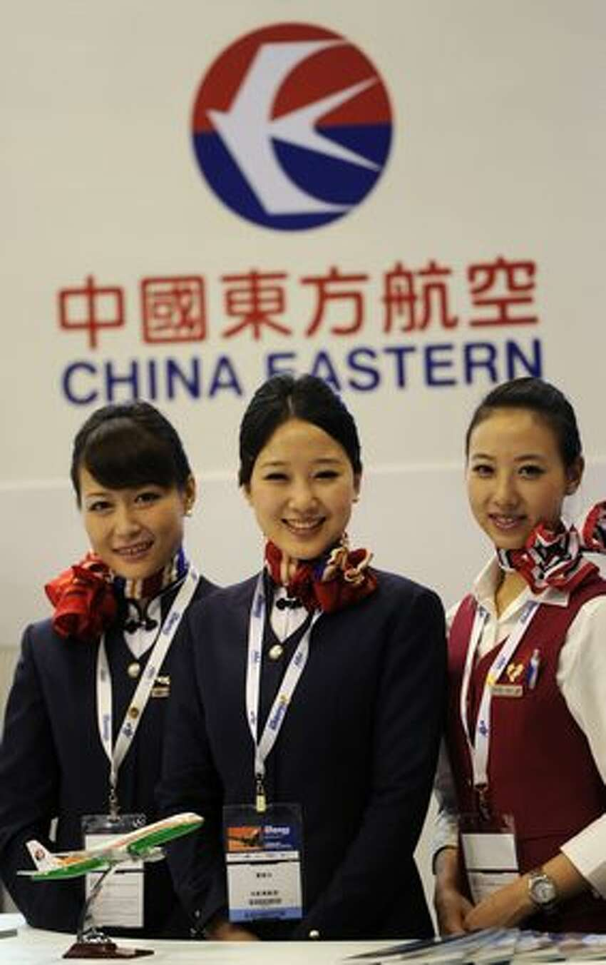 Staff wait for inquiries at a China Eastern stand at the Asian Aerospace exhibition in Hong Kong.