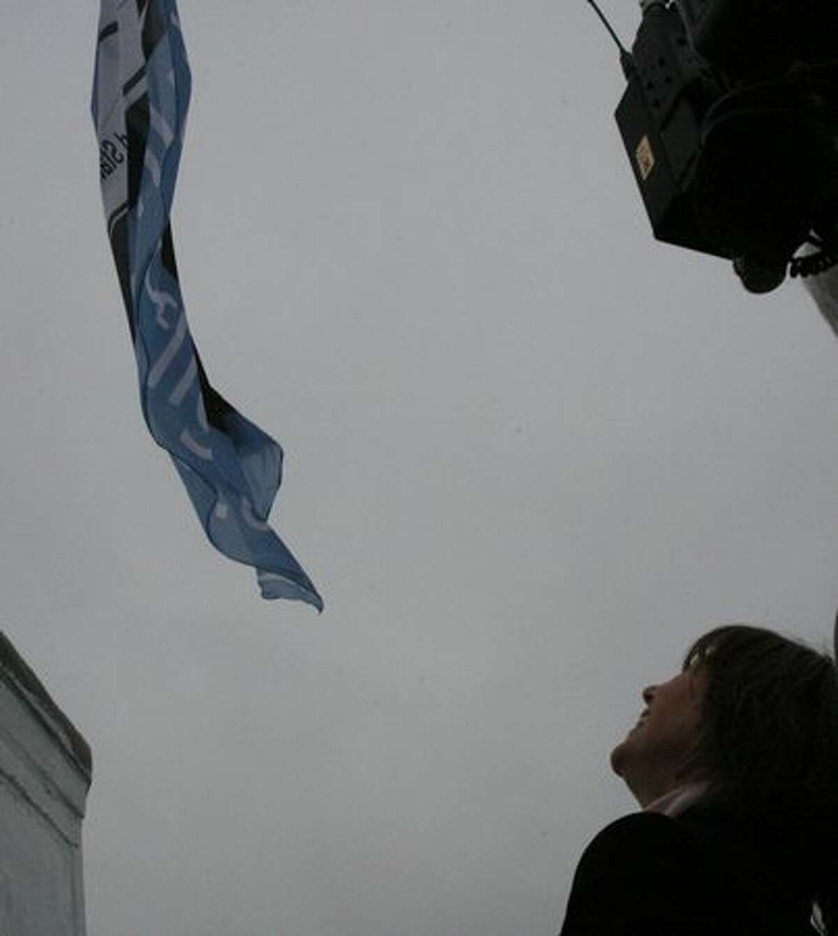 Wings over Washington Executive Director Bonnie Dunbar looks at the Museum of Flight's space shuttle flag after raising it over Seattle's Space Needle.