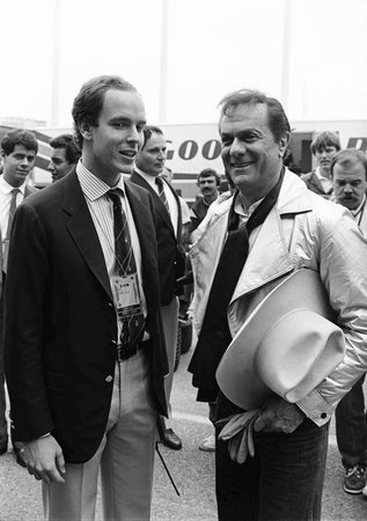 Prince Albert of Monaco chats on May 19, 1985, in Monaco with American actor Tony Curtis, in the pits, during the warm-up, a few hours before the start of the Monaco Formula 1 Grand Prix. (FILM) AFP PHOTO GABRIEL DUVAL